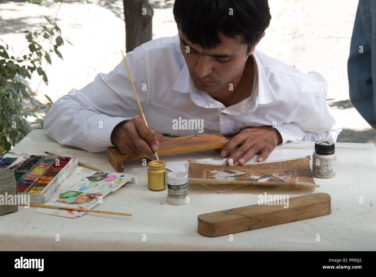 An Uzbek man painting crafts in Uzbekistan, Silk Road, Central Asia Stock Photo
