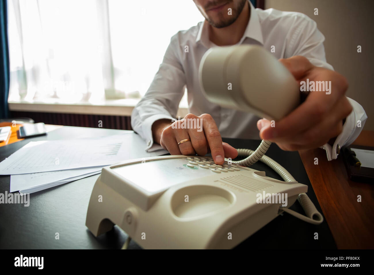 Businessman dialing a telephone number in order to make a phone call. - Stock Image