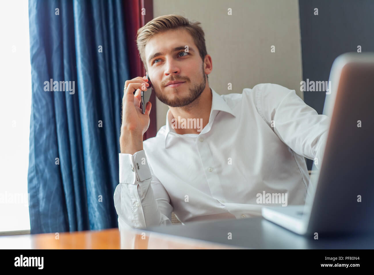 Portrait of handsome young entrepreneur speaking by phone and using laptop while working in comfortable hotel room or office. - Stock Image