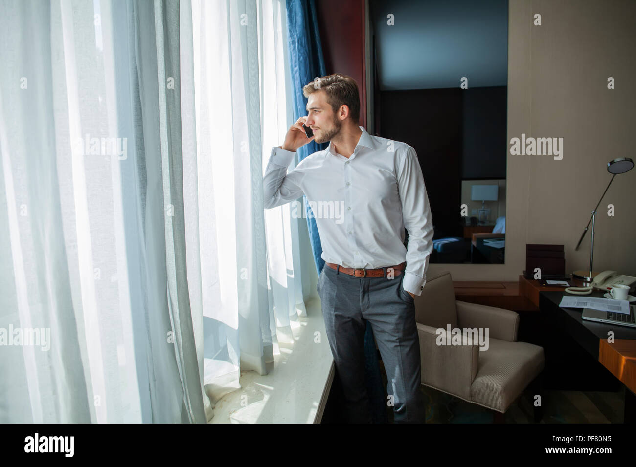 Caucasian mid adult businessman talking with mobile telephone in hotel room during business trip. - Stock Image
