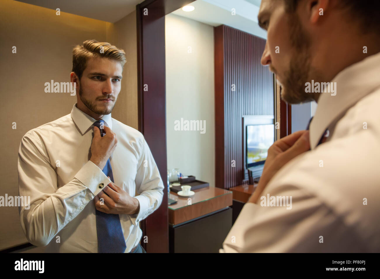 People, business,fashion and clothing concept - close up of man in shirt dressing up and adjusting tie on neck at home. - Stock Image