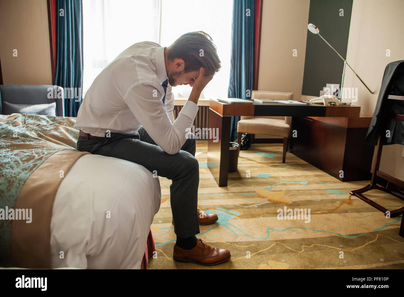 Frustrated young man in formal suit sitting on bed besides luggage bag. Businessman thinking about problems in business or at home, not feeling well, lost job, relationships or work related stress - Stock Image