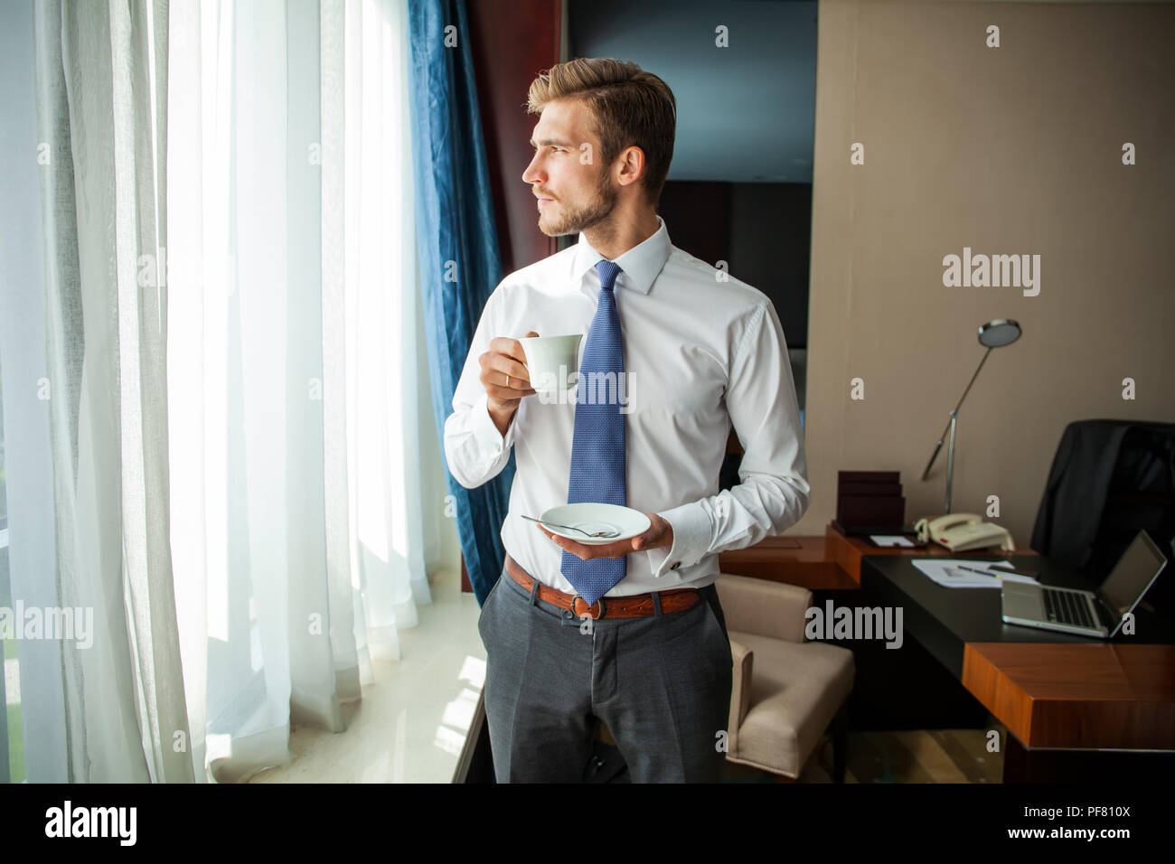 business trip and people concept - businessman drinking coffee at hotel room. - Stock Image