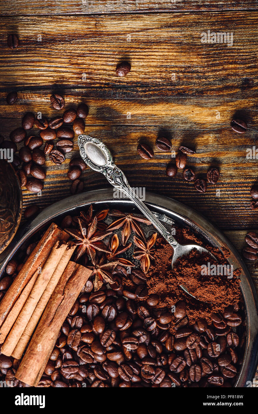 Coffee Beans with Spooonful of Ground Coffee, Cinnamon Sticks and Star Anise on Plate. Some Beans Scattered on Wooden Table. View from Above. Vertical - Stock Image