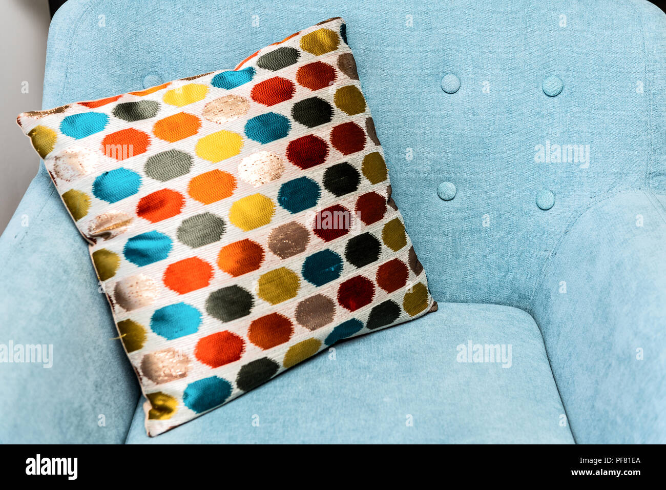 Closeup of blue comfortable, new, teal, turquoise armchair, chair with colorful, multi colored pillow, cushion with nobody - Stock Image