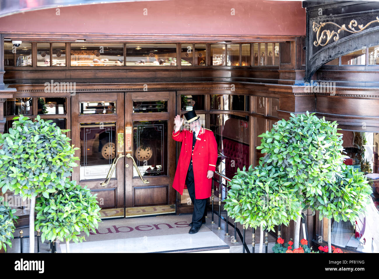 London, UK - June 22, 2018: Porter, doorman in traditional attire, clothing, hat, red gown, coat standing at Rubens hotel, inn entrance waving hand - Stock Image