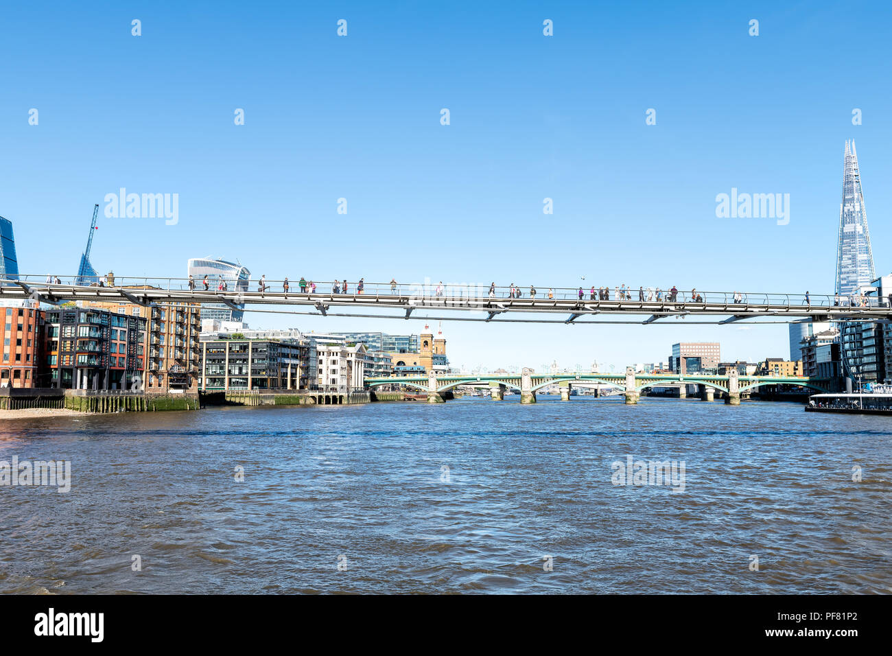 London, UK - June 22, 2018: View from boat on Thames on Millennium Bridge with people, pedestrians walking during sunny day with sunlight, clear blue  Stock Photo