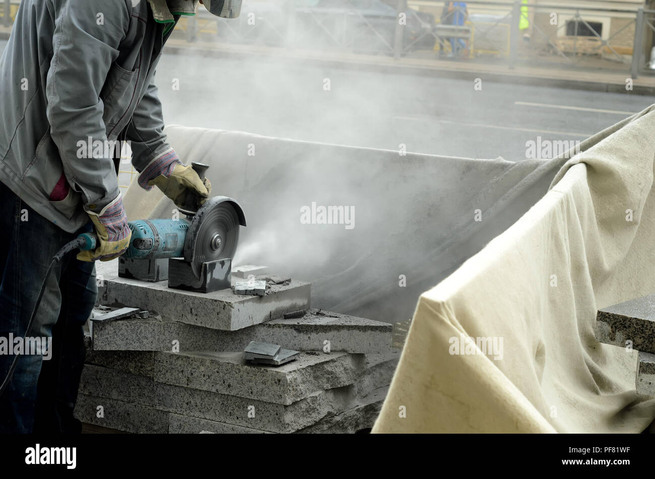 The worker cuts a big powerful angle grinder paving slabs. - Stock Image