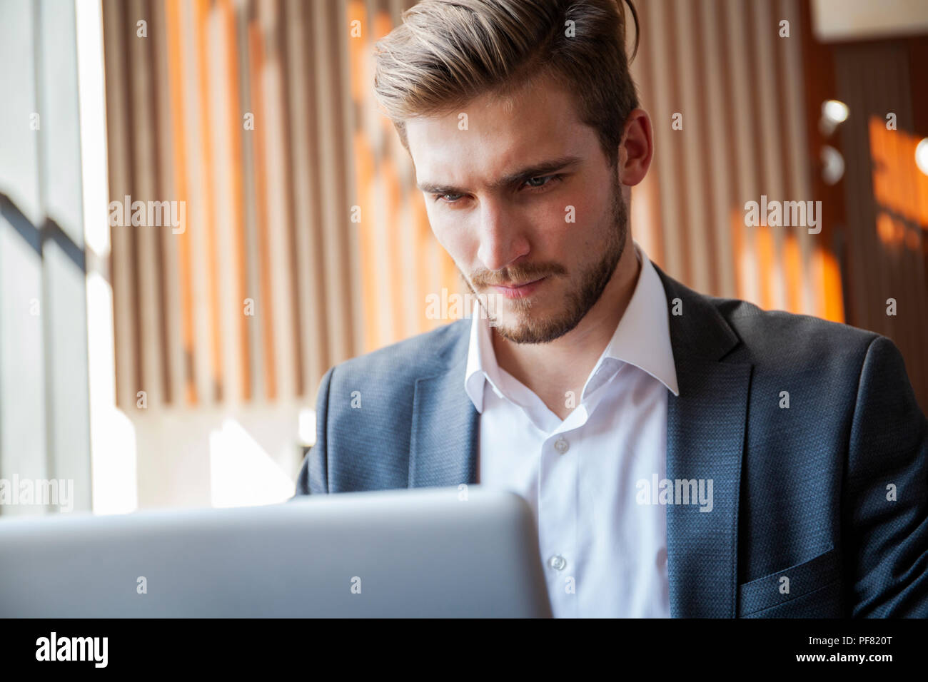Young businessman working on laptop, sitting in hotel lobby waiting for someone. - Stock Image