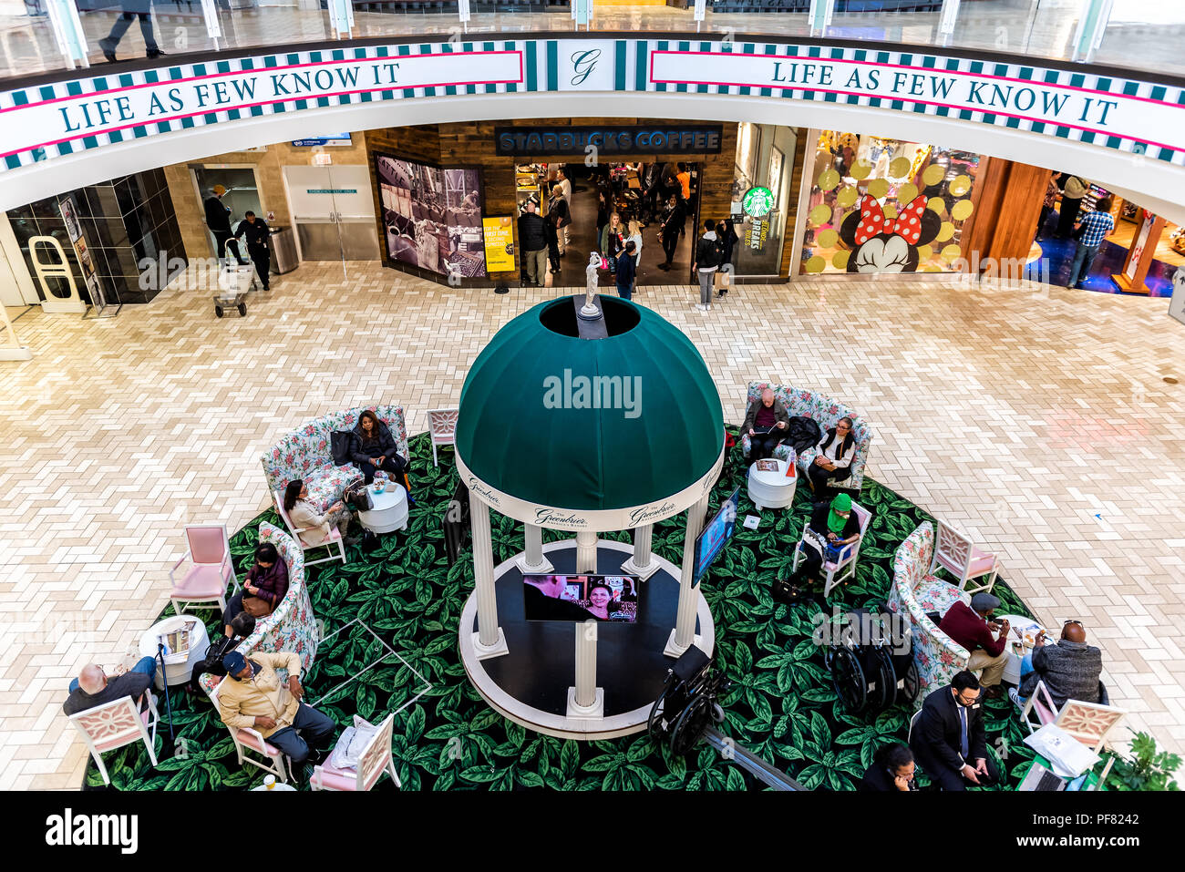 Tysons Corner, USA - January 26, 2018: High angle view on people, shoppers, customers relaxing on couches, armchairs, chairs in plaza, court of indoor - Stock Image
