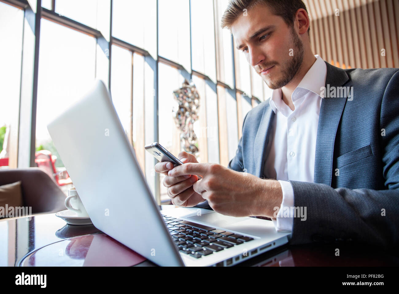 Businessman in black suit using mobile smart phone and working on laptop computer, browsing internet and writing on paper notebook in modern office. Man working on electronics devices with copy space - Stock Image