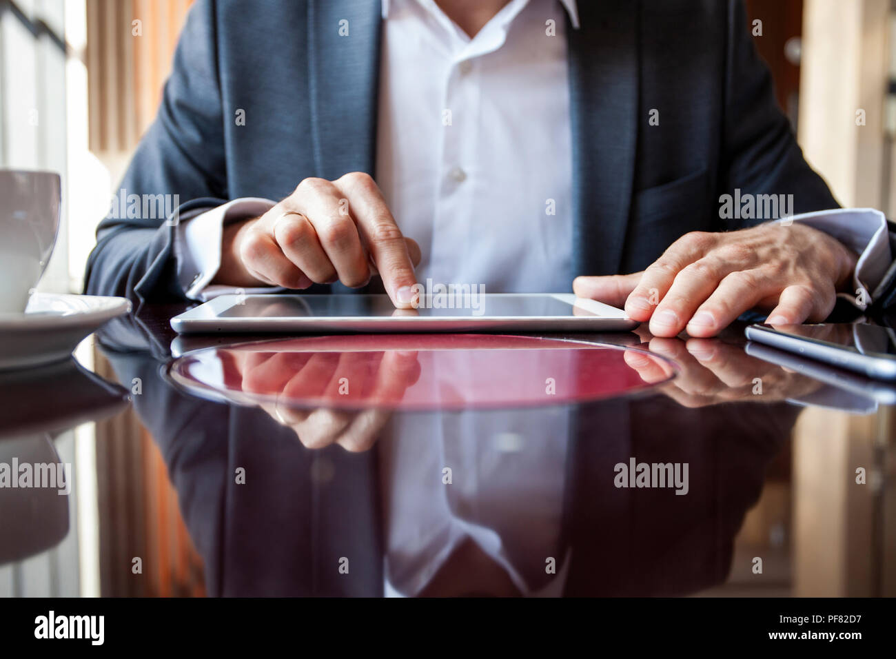 Businessman holding digital tablet, hands multitasking man using tablet - Stock Image