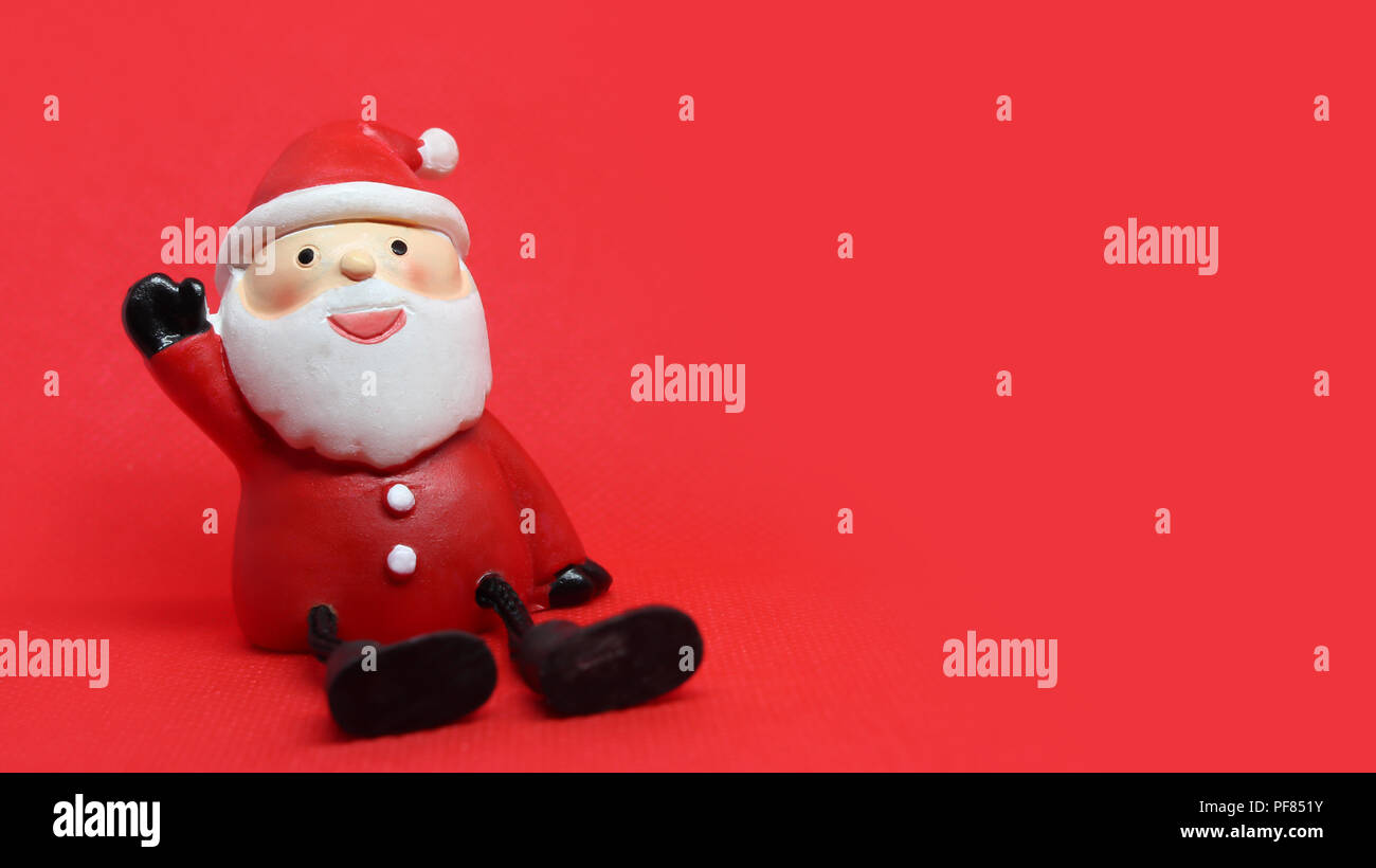 9258d61130555 Cute santa doll in red textured background with copyspace to the right