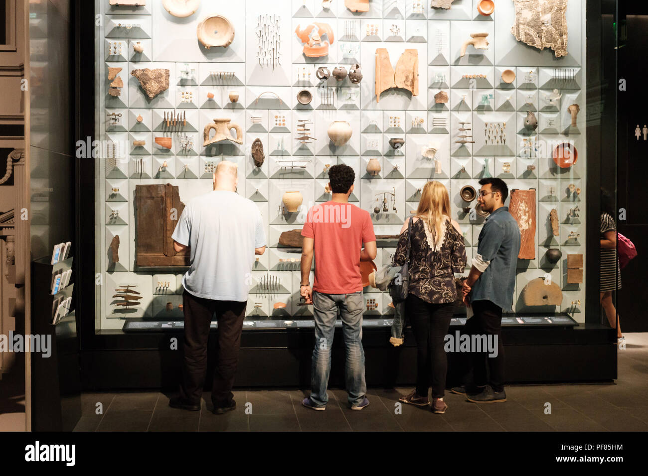 Visitors examine a display case of Roman artifacts found during the restoration of the Temple of Mithras, London Mithraeum, City of London Stock Photo