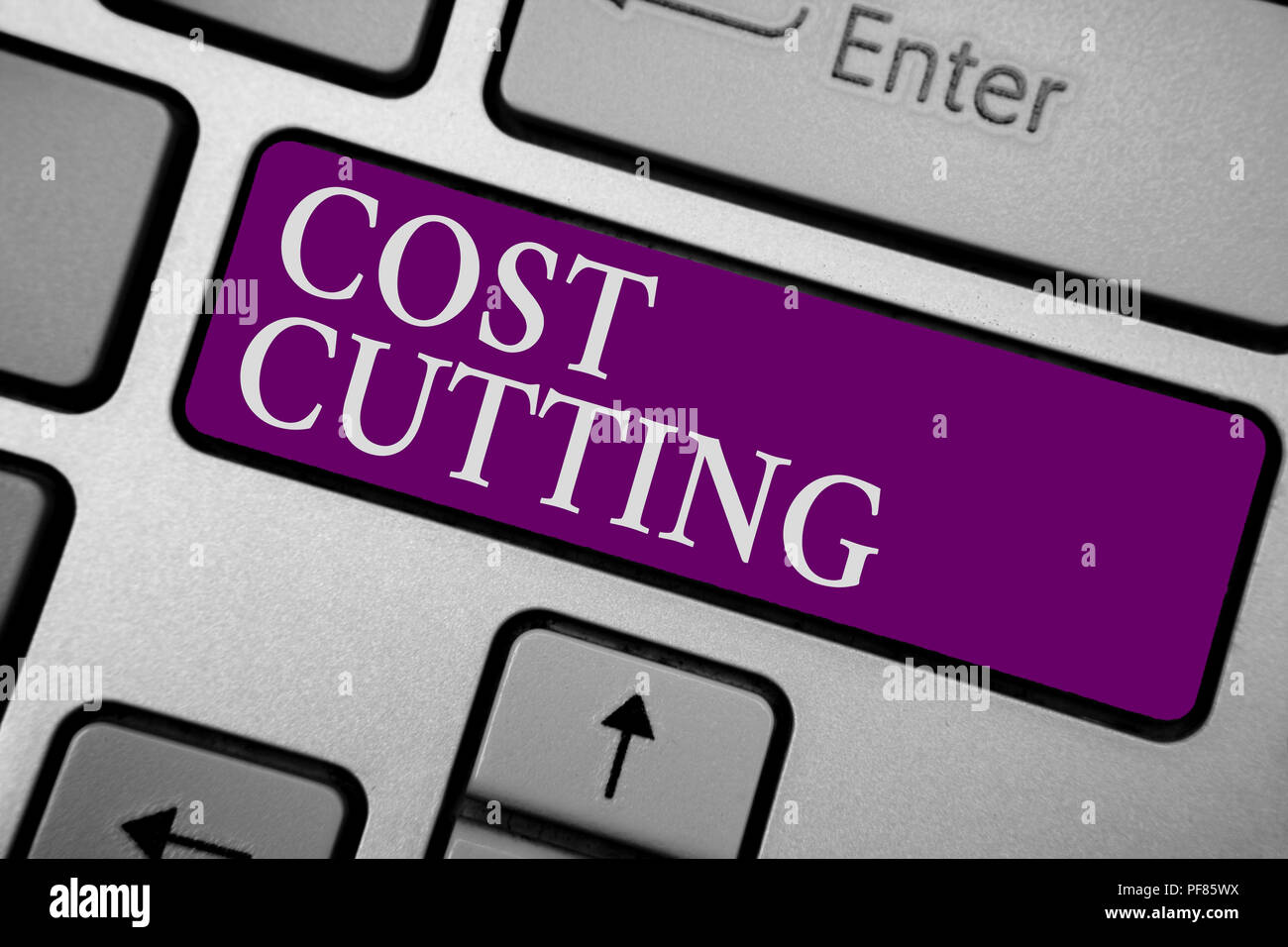 Writing note showing Cost Cutting. Business photo showcasing Measures implemented to reduced expenses and improved profit Keyboard purple key Intentio - Stock Image