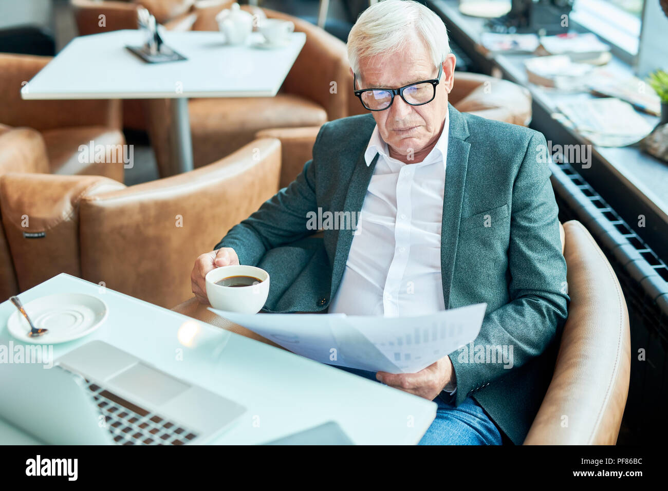 Senior Businessman Working in Cafe - Stock Image