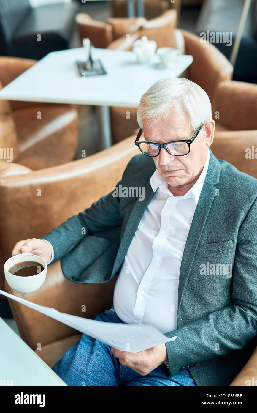 Modern Senior Businessman Working in Cafe - Stock Image