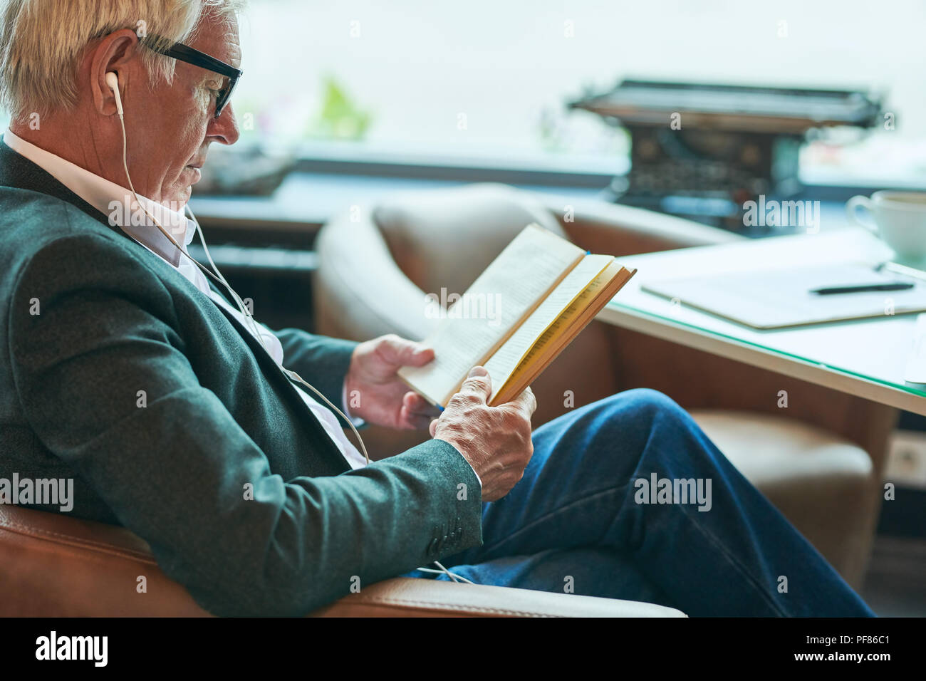 Contemporary Senior Man Reading in Cafe - Stock Image