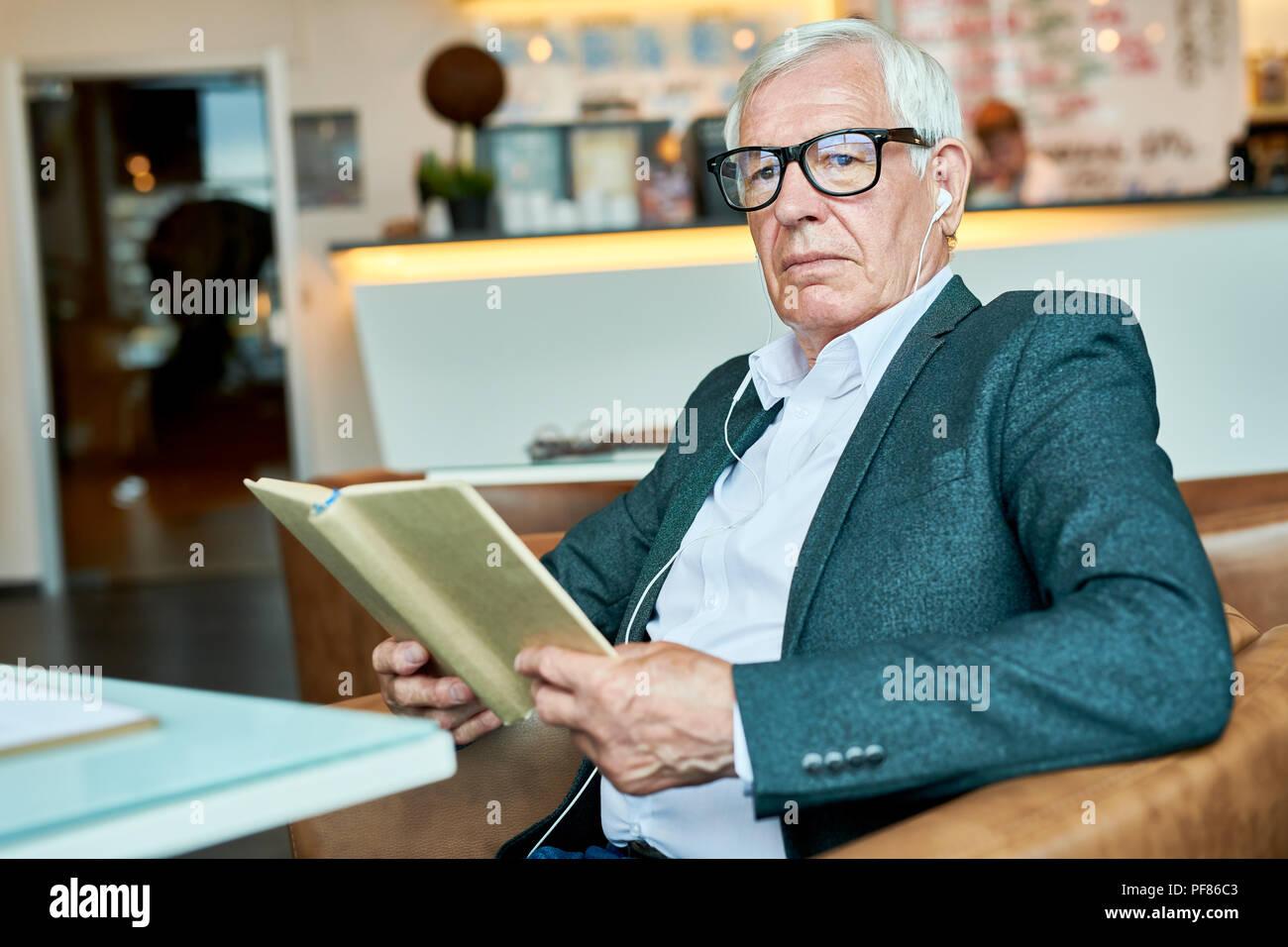Pensive Senior Man Reading Book in Cafe - Stock Image
