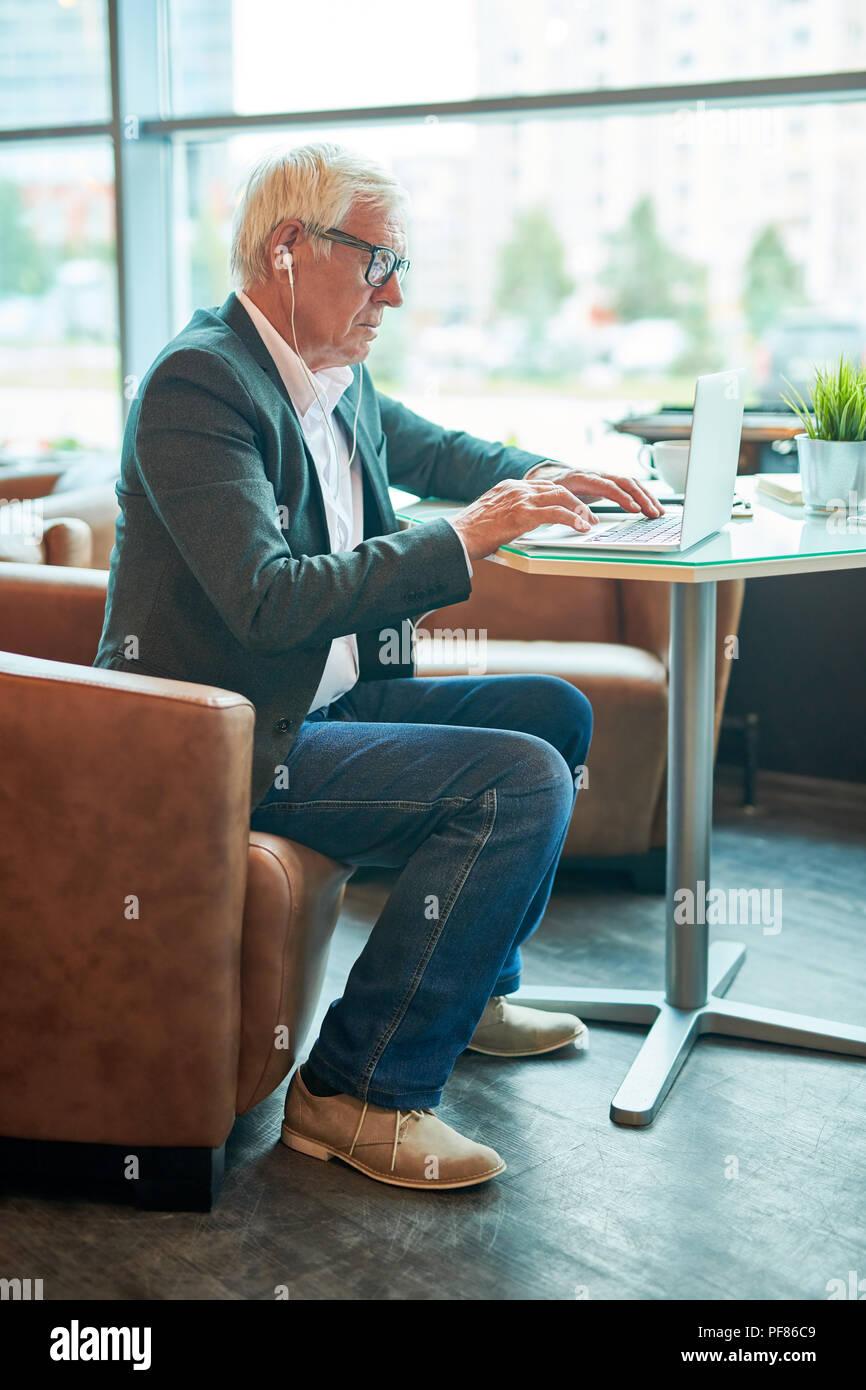 Senior  Businessman Using Internet in Cafe - Stock Image