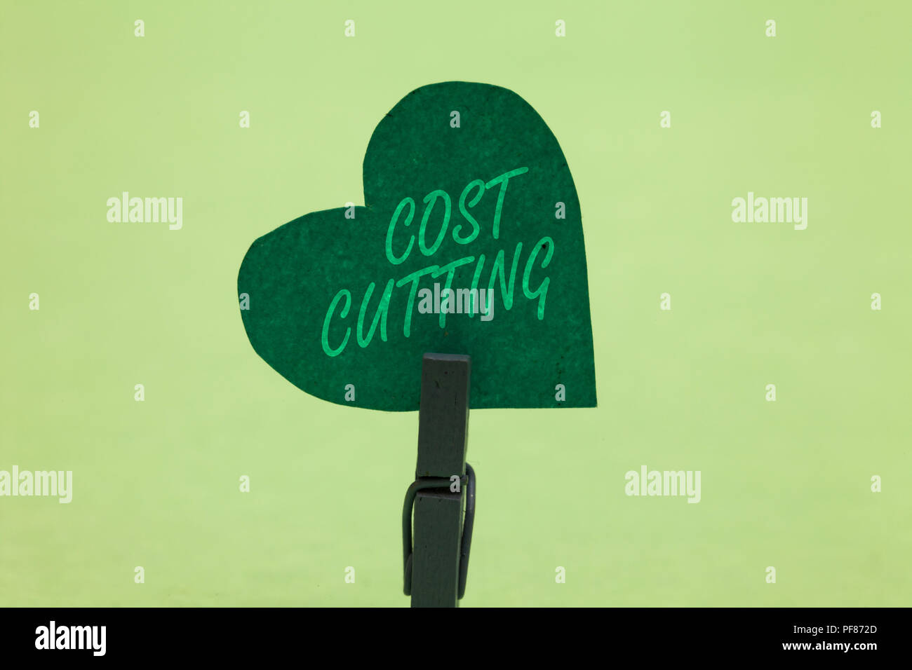 Writing note showing Cost Cutting. Business photo showcasing Measures implemented to reduced expenses and improved profit Clothespin holding green pap - Stock Image