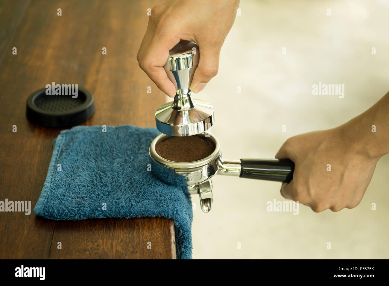 Barista pressing ground coffee into portafilter using tamper with blue cloth on the table Stock Photo