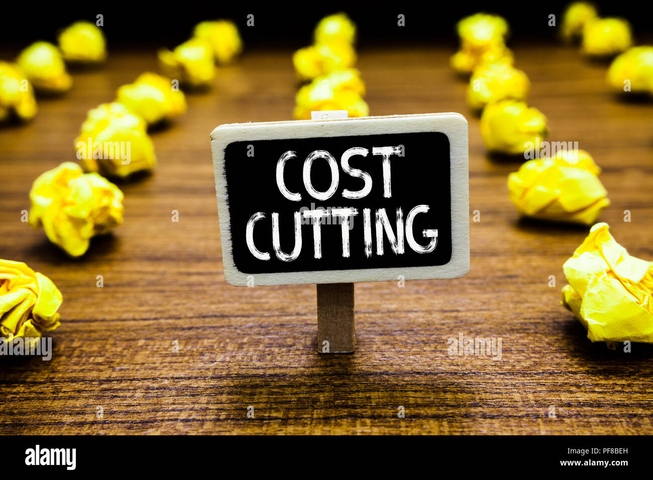 Handwriting text Cost Cutting. Concept meaning Measures implemented to reduced expenses and improved profit Blackboard crumpled papers several tries m - Stock Image