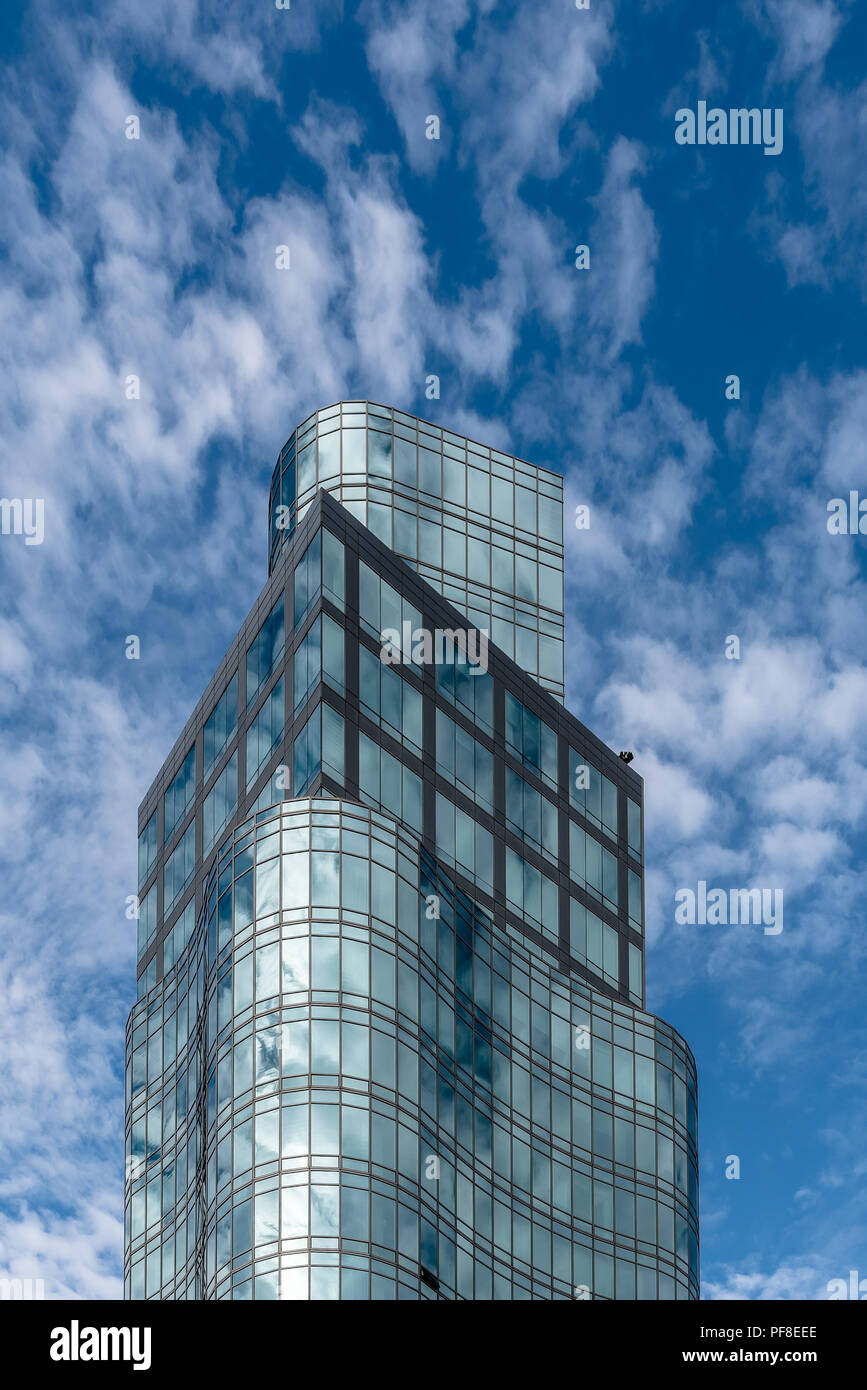 New York City, USA - June 20, 2018:  Low angle view of modern skyscraper against sky in Manhattan. Clouds reflected in glass facade Stock Photo