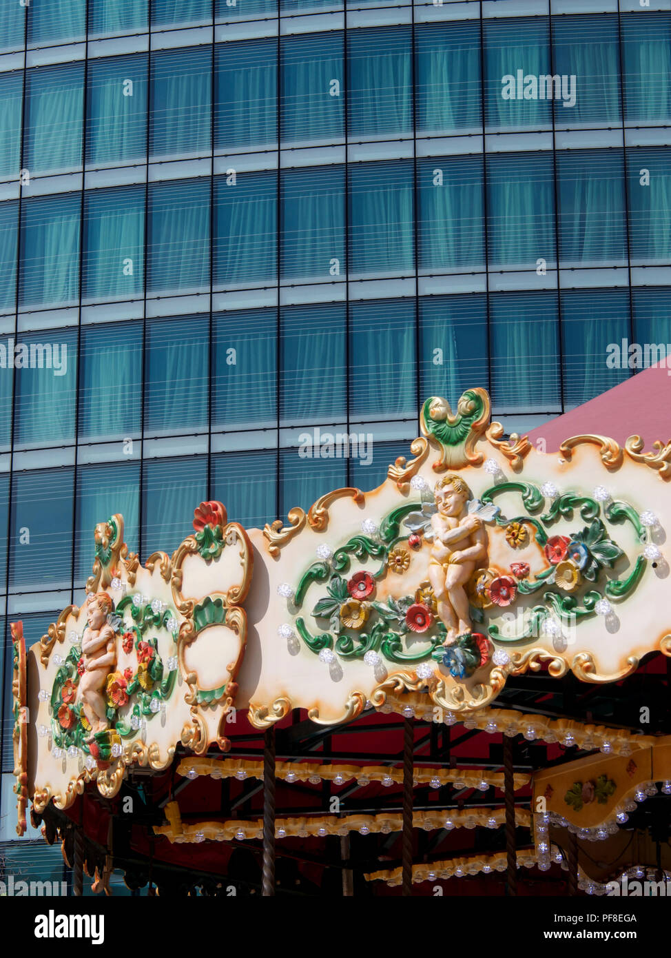 Close-up of the top decorated with a carousel in front of a glass building. France - Stock Image