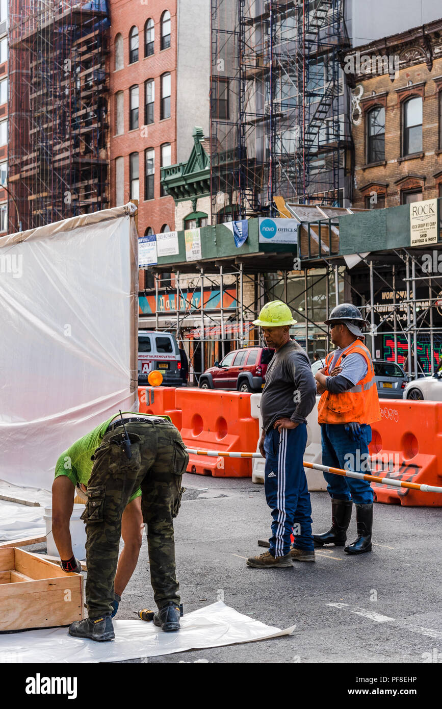 New York City, USA - June 20, 2018: Three workers working on construction site in street in New York City - Stock Image
