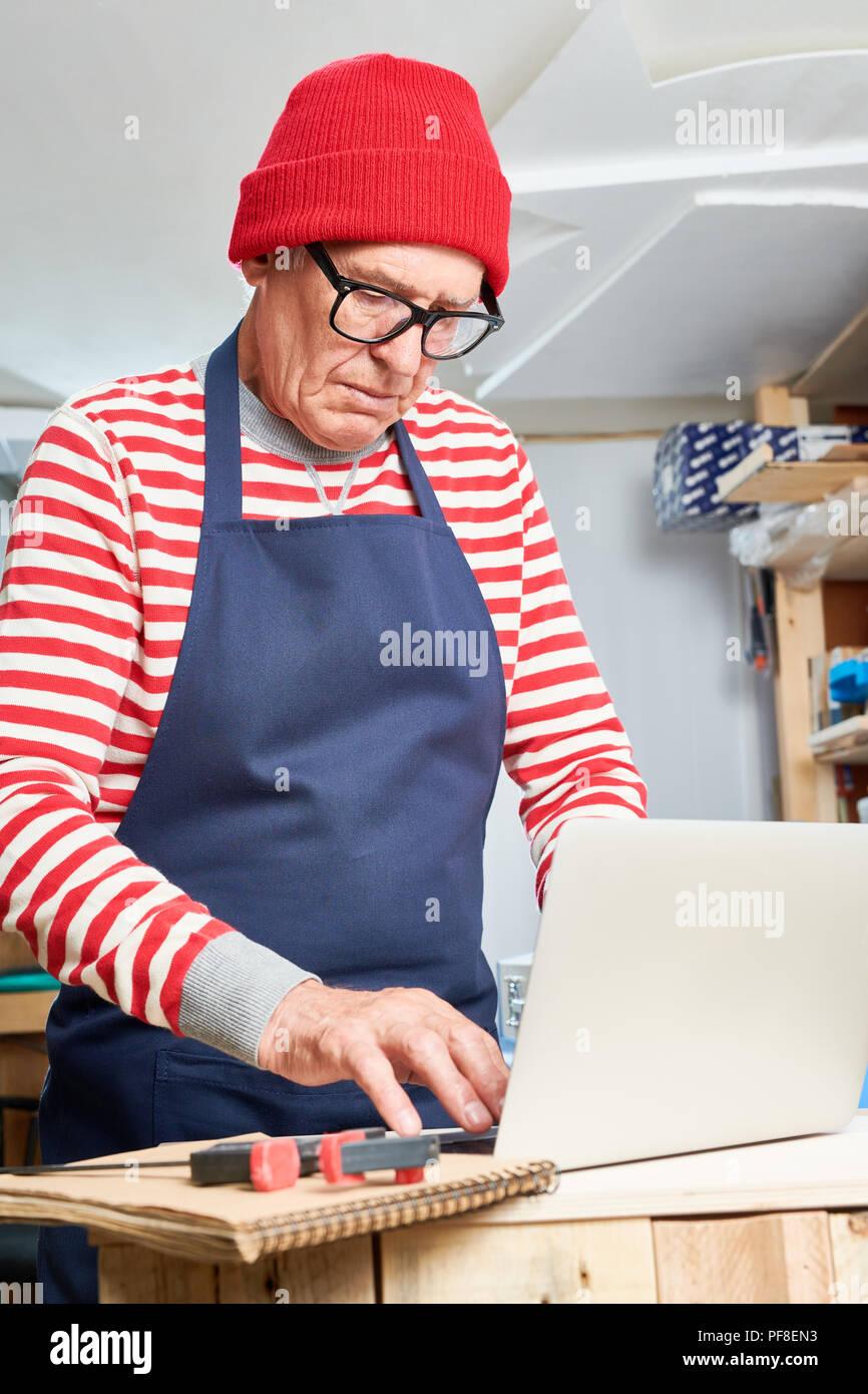 Elderly craftsman using laptop - Stock Image