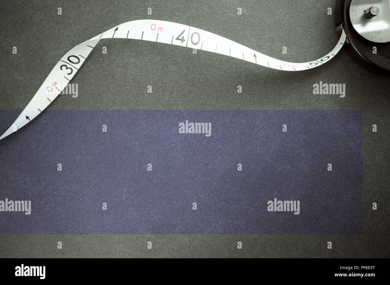 industrial metric measuring tape on a dark worktop surface - top view - Stock Image