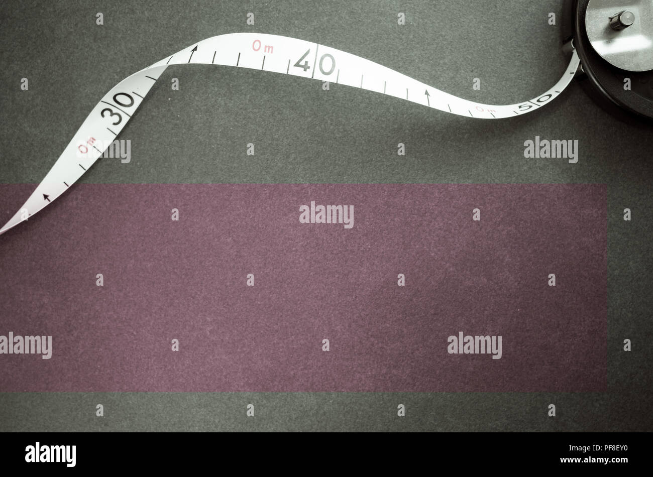 industrial metric measuring tape on a dark worktop surface - top view - Stock Image