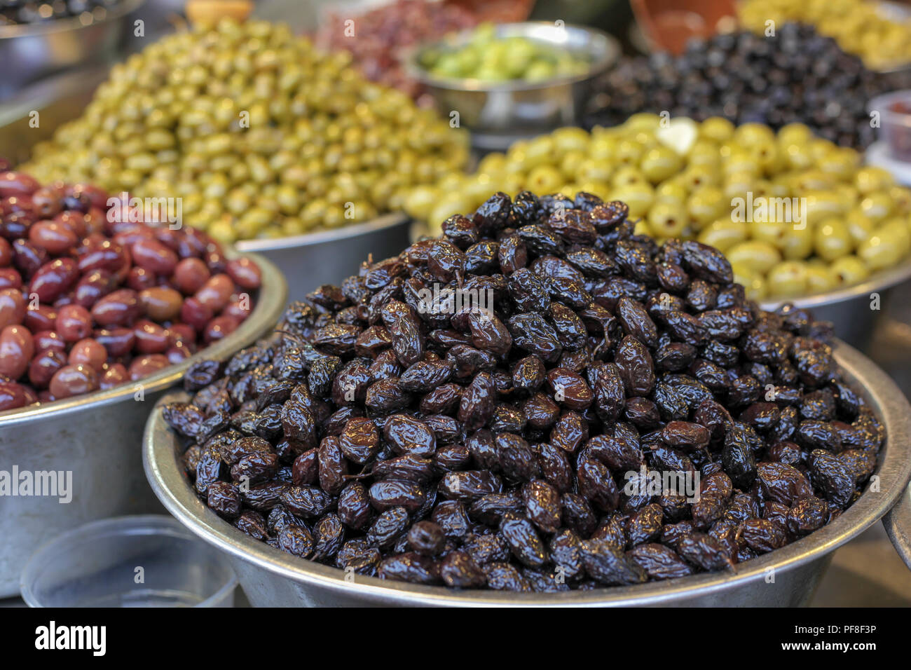 Olives of different types and colours in a market stall Photographed in Tel Aviv, Israel Stock Photo