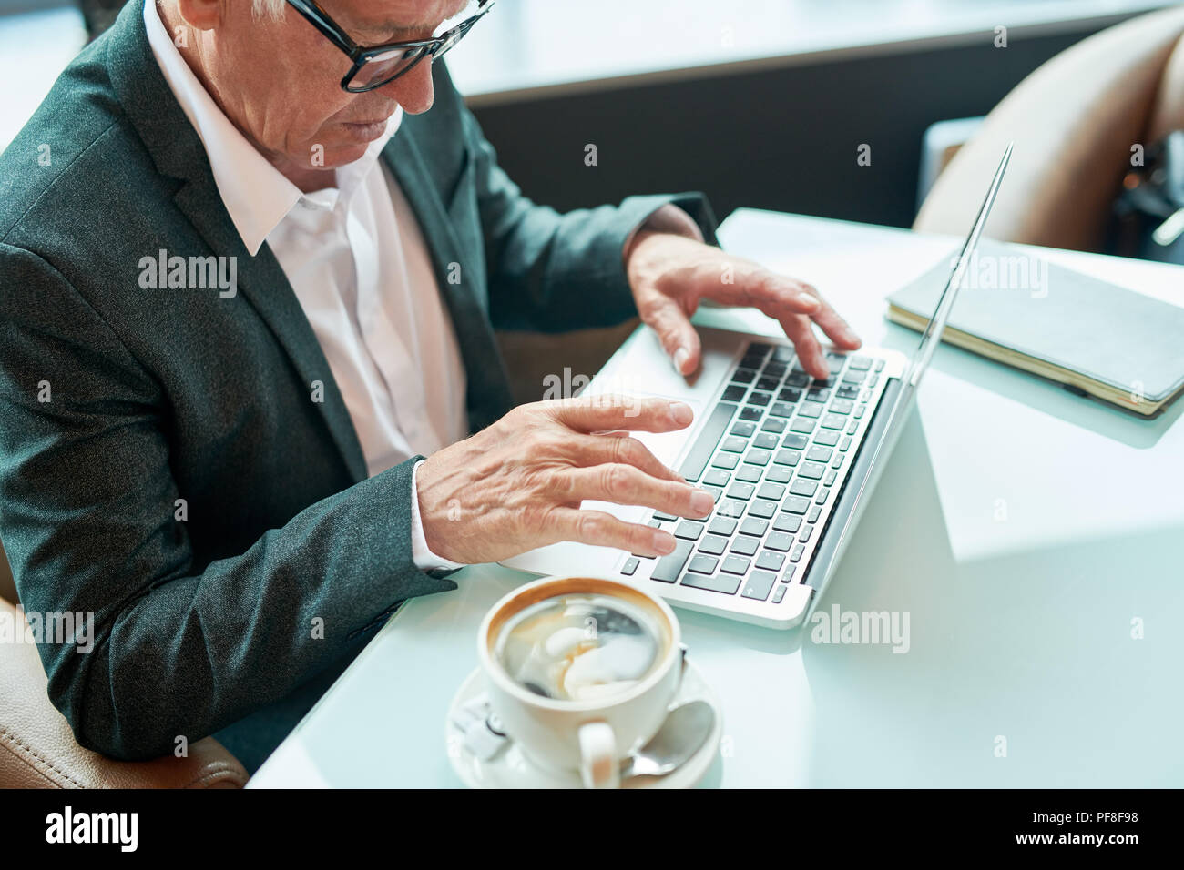 Elderly businessman using laptop in cafe - Stock Image