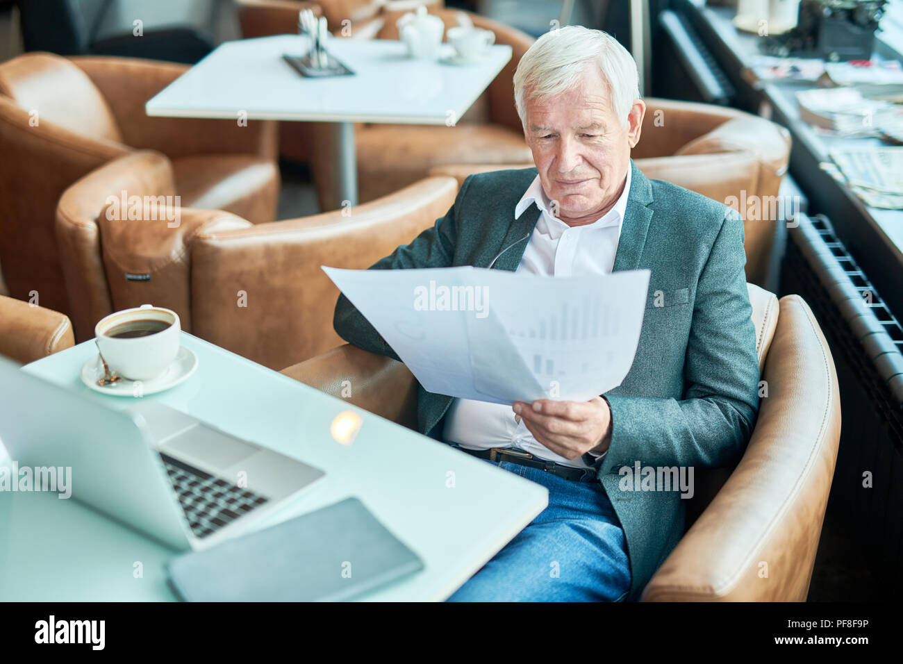 Aged businessman reading documents in cafe - Stock Image