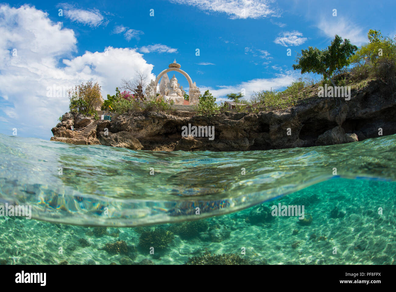 Underwater split-level photo in shallow tropical water of Buddhist temple & Ganesh statue at Menjangan Island, Bali, Indonesia, with blue sky above. - Stock Image