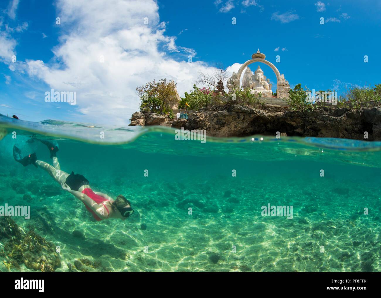 Underwater split-level photo of a female tourist snorkeller & Buddhist temple & statue of Ganesh above, at Menjangan Island, Bali, Indonesia - Stock Image