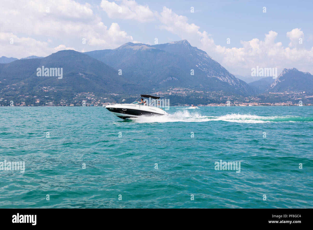 Fast speedboat on Lake Garda in front of mountains.  The powerboat has a bow wave and a wake and is moving right to left - Stock Image