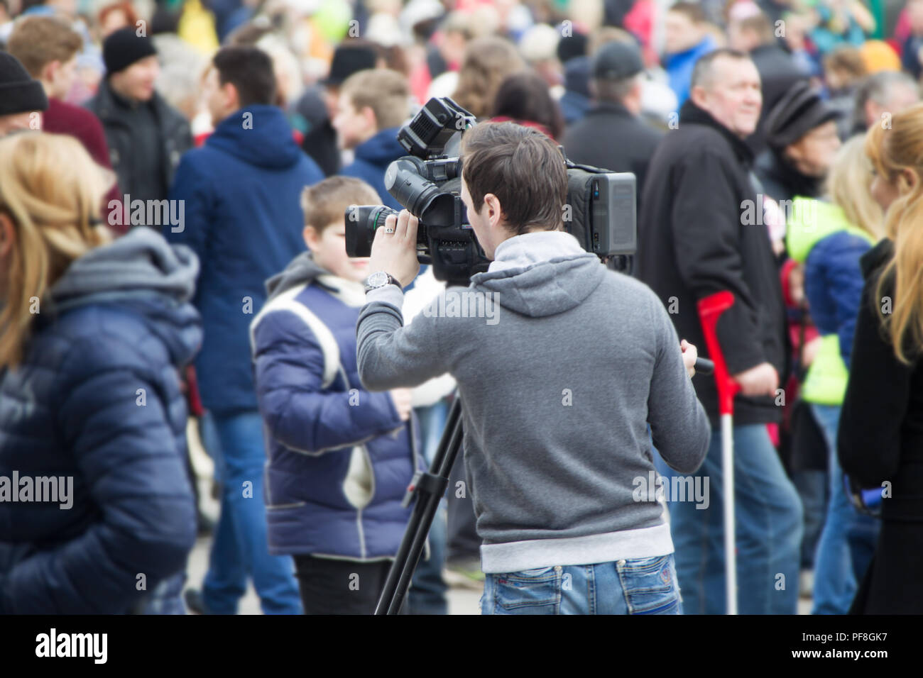 Belarus, Gomel, Central district. The cameraman shoots a crowd of people. News reporter - Stock Image