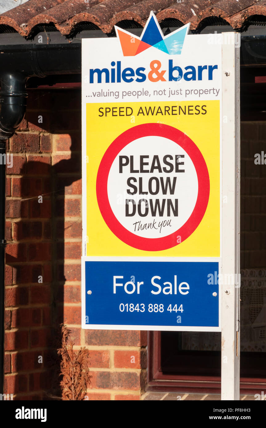 Speed Awareness Please Slow Down message incorporated into an estate agent's For Sale board. - Stock Image