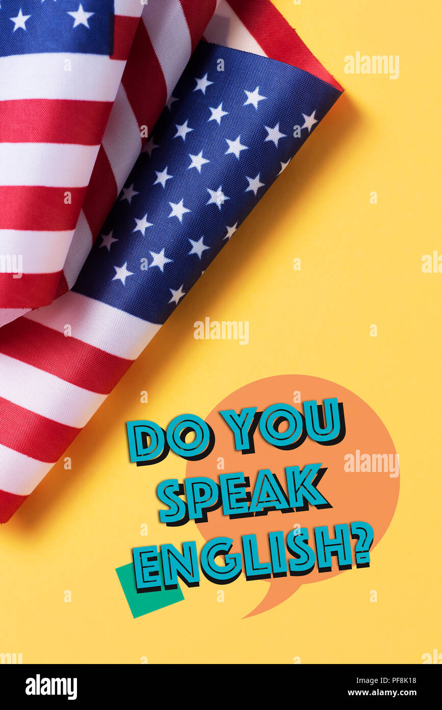 some flags of the United States and the question do you speak English? on a yellow background Stock Photo