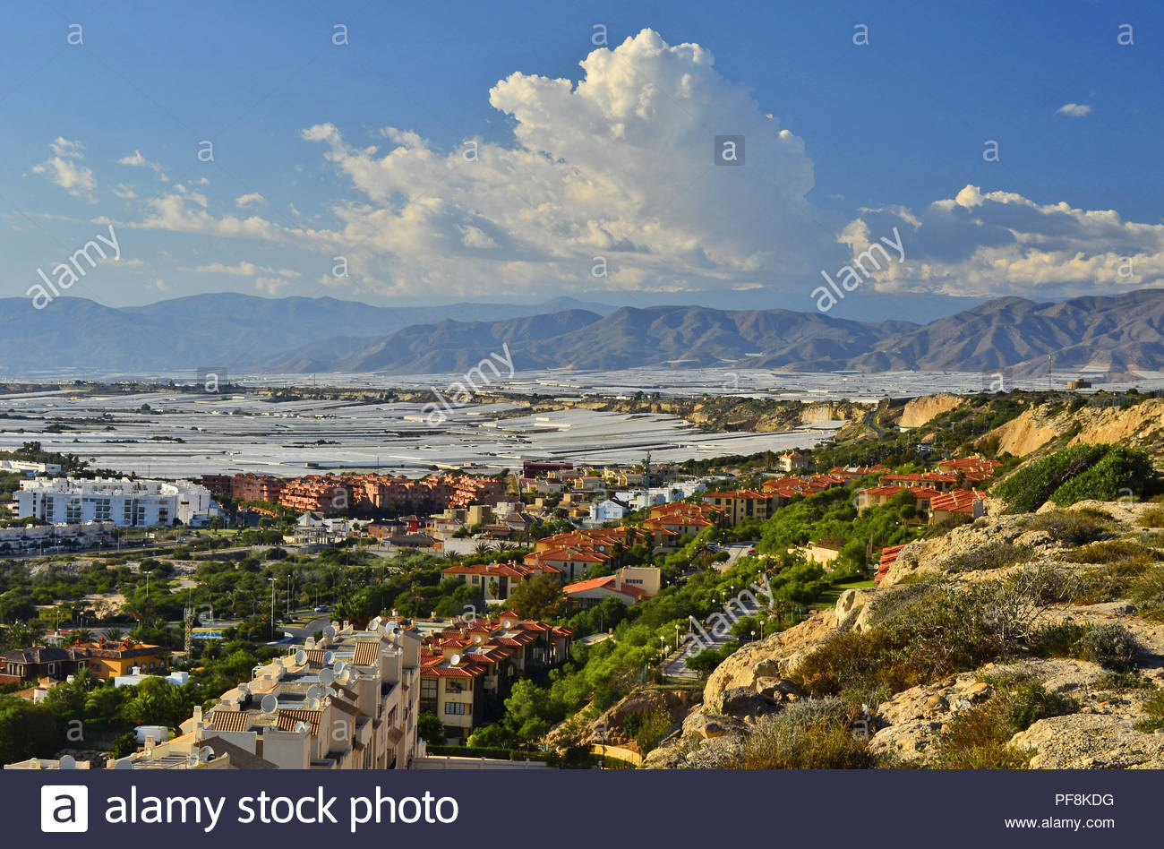 Two main industries of Almeria Southern Spain - tourism and agriculture. Green valley with hotel apartments and field of greenhouses in background. - Stock Image