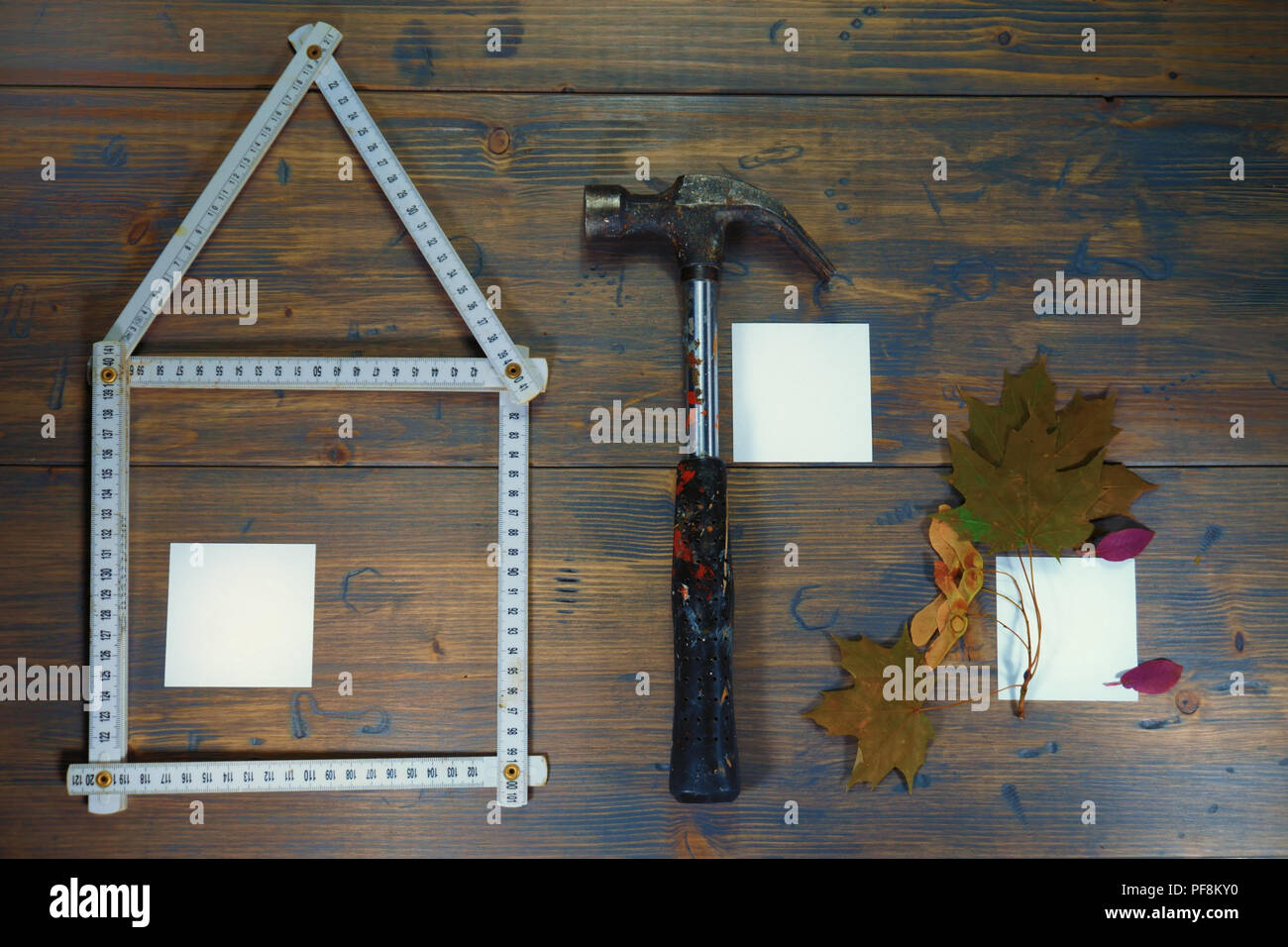 Conceptual construction and renovation still life with a flat lay design of a house formed by a ruler, hammer and autumn leaves with blank sticky note Stock Photo