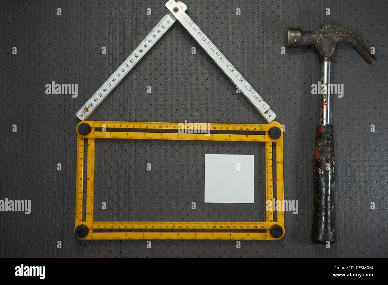 Conceptual construction and renovation still life with a flat lay design of a house formed by a yellow and white rulers, hammer and blank sticky notes - Stock Image