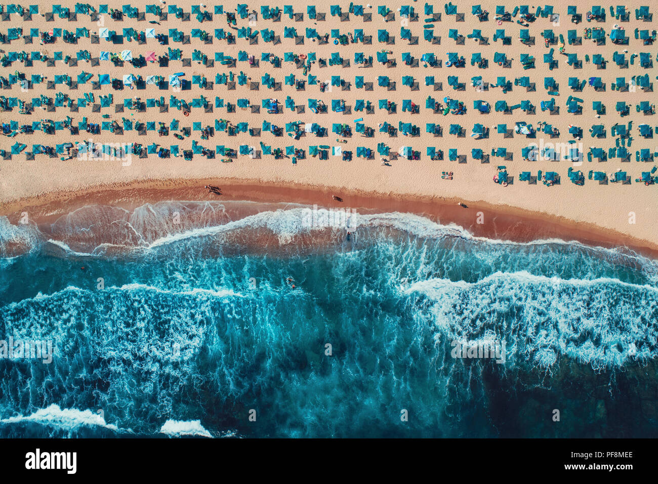 Aerial top view on the beach. Umbrellas, sand and sea waves - Stock Image