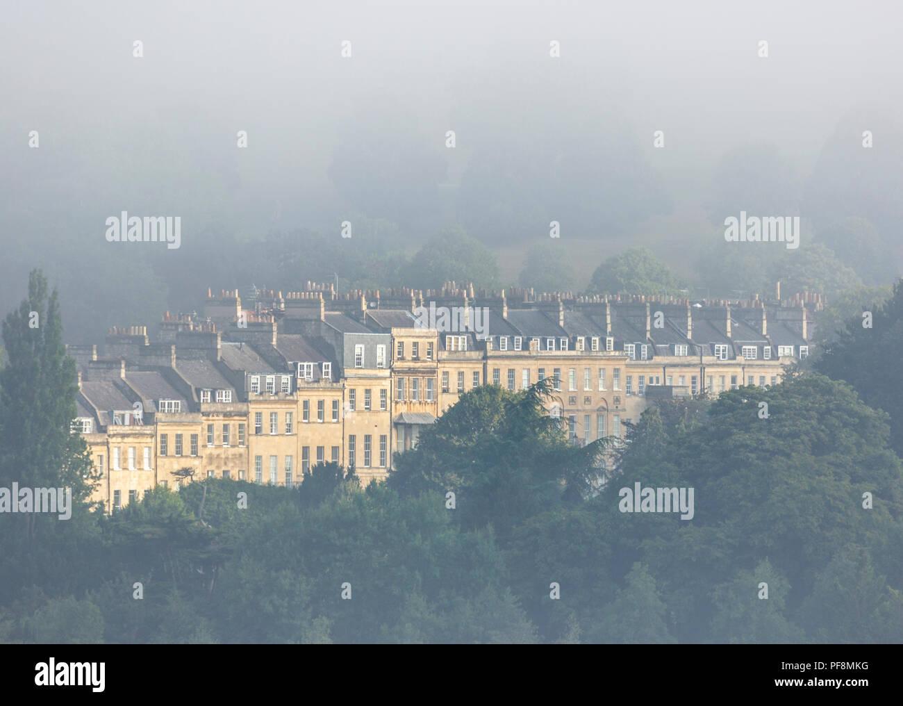 A row of terraced Georgian buildings shrouded in morning mist  in Bath, UK - Stock Image