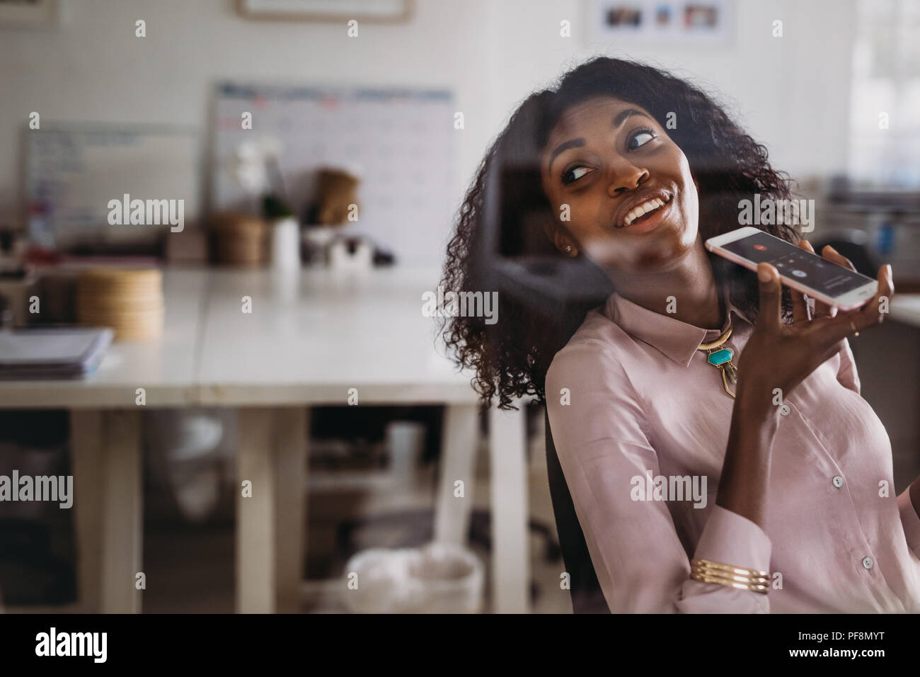 Businesswoman in formal attire talking over mobile phone on loudspeaker sitting at home and looking back. Woman entrepreneur managing business from ho - Stock Image