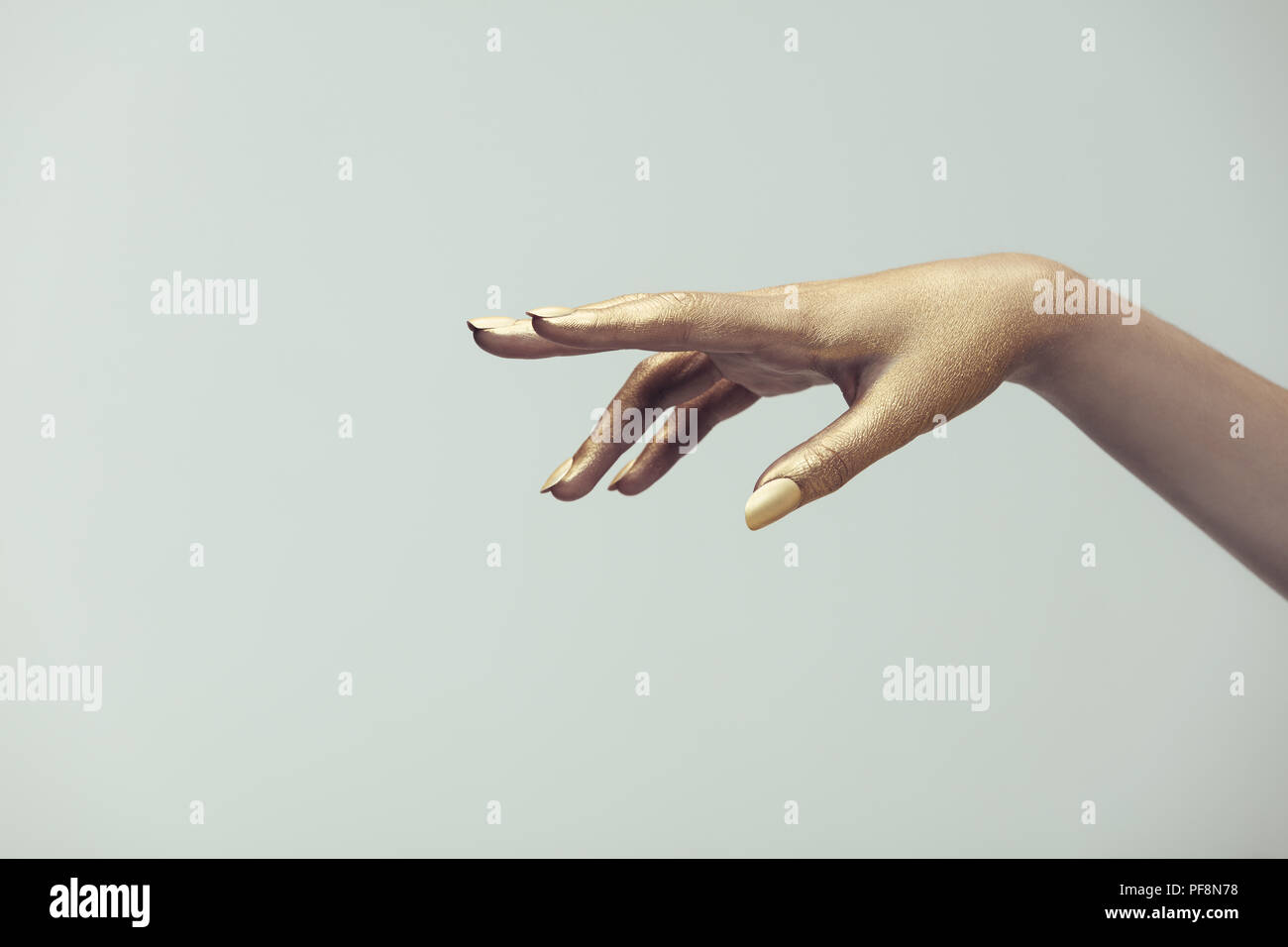 One hand of female in gold paint on grey background  Hand of
