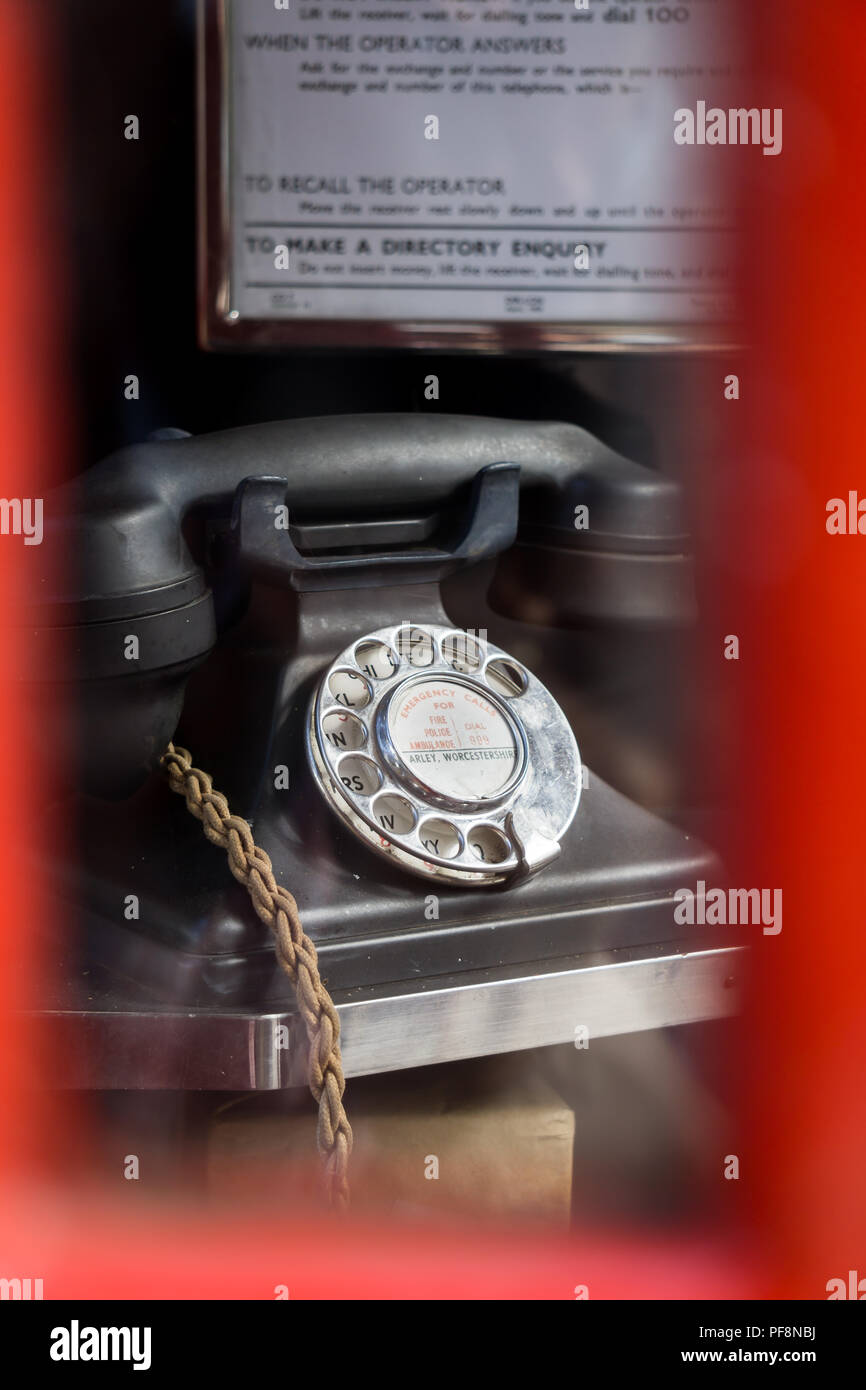 Close up of black vintage GPO bakelite telephone viewed through glass of disused red telephone box. Alpha numeric dial face, braided handset cord. - Stock Image